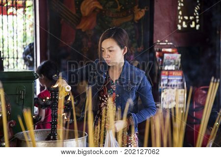 Ho Chi Minh City, Vietnam - March 26, 2017: People praying and burning incence stick in Quan Am Pagoda, named after the Goddess of Mercy, in Cholon, the Chinatown area of Saigon