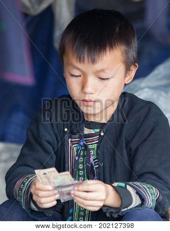 SA PA, VIETNAM - AUGUST 2017: Portrait of black hmong ethnic minority boy in Sa Pa town, the high mountains, Lao Cai province, Vietnam