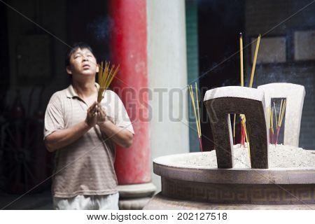 Ho Chi Minh City, Vietnam - March 26, 2017: Man praying and burning incence stick in Thien Hau Pagoda, dedicated to the Chinese sea goddess Mazu , in Cholon, the Chinatown area of Saigon