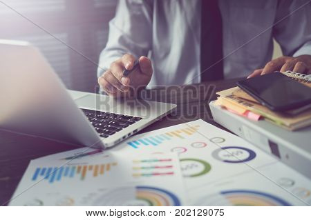 businessman hand working smart phone on wooden desk in office in morning light. The concept of modern work with advanced technology. vintage effect.