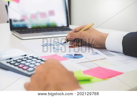 Business Man Hands Pointing And Working With Financial Paperwork And Laptop Computer On Wooden Desk