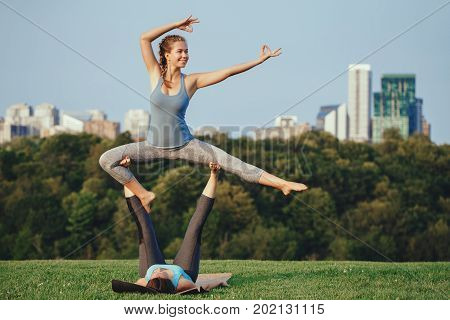 Two young beautiful Caucasian women yogi doing ninja acro yoga pose. Women doing stretching workout in park outdoors at sunset. Healthy lifestyle modern activity