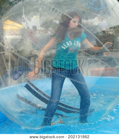Denver, Colorado - September 17, 2011: girl in a transparent ball on the water trying to keep balance