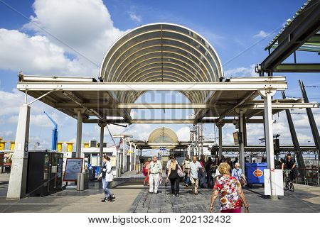 OOSTENDE BELGIUM - JUNE 22 2016: Entrance of the Oostende railway station with people passing by vending machines in a sunny day with clouds. Oostende Belgium