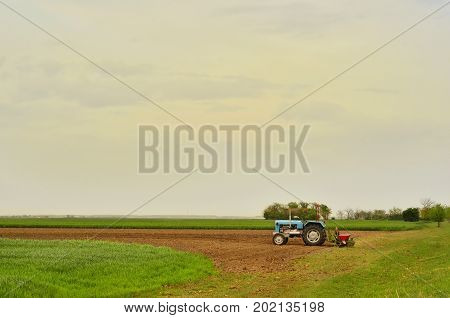 Tractor with seeder machinery in Farm Field Agricultural Landscape.
