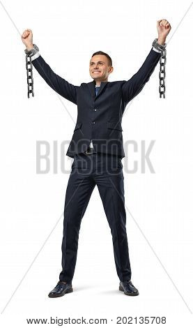 A happy businessman with hands raised up showing broken shackles on white background. Break free. Free business. Unlimited career.