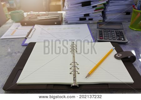 Business And Finance Concept Of Office Working, Opened Blank Notebook And Pencil With Pile Of Unfini