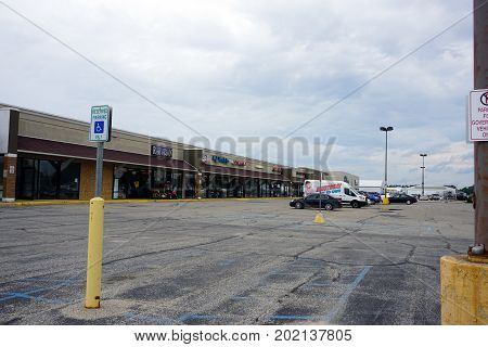 CADILLAC, MICHIGAN / UNITED STATES - JUNE 22, 2017: The Village at Wexford Shopping Center houses Universal Rent-to-Own, Miracle Ear, Rose Nails, Golden Shears and Discount Tobacco.