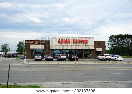 CADILLAC, MICHIGAN / UNITED STATES - JUNE 22, 2017: One may eat Chinese food at the Asian Buffet restaurant, and drink coffee at the Biggby Coffee shop, on Mitchell Street.