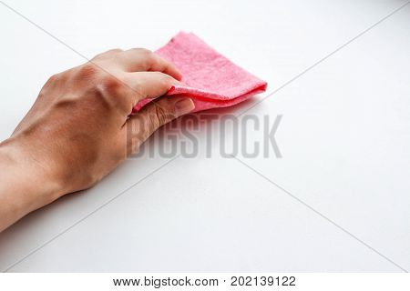 Female Hand Wiping The Dust Pink Cloth. Wet Cleaning. Closeup. Isolated On A White Background