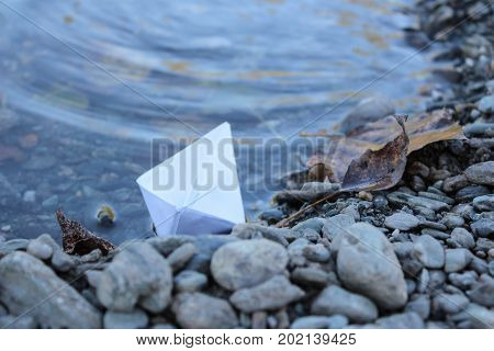 Paper Boat In The River. Paper Boat On The Shore In The Water. Closeup
