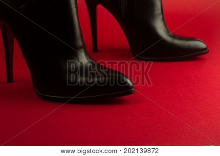 horizontal closeup of high heel woman black leather stylish pair of shoes on red background