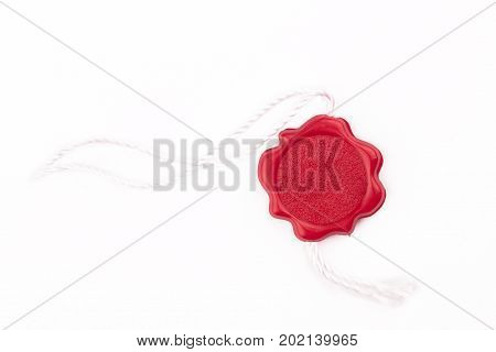 top view of empty red wax plastic seal swing tag with fiber thread and copyspace isolated on white background