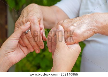 Close up young caregiver holding elderly female's trembling hands Parkinson disease