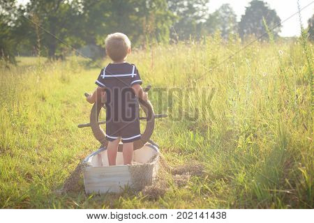 Boy in blue sailor suit playing with steering wheel in the boat, pretending to sail across summer sea of grass. Adventure, children activity, game.