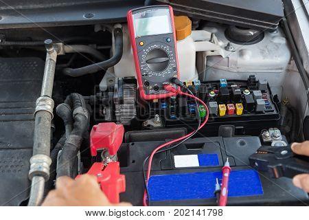 Check the carElectrician measuring voltage in distribution board closeup