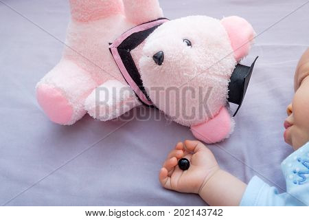 Teddy bear's eye was detached by toddler and in sleeping 10 months old baby hand poorly attached button was removed by kid beware of choking hazard for children concept warning for parent