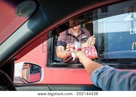 Bangkok Thailand - Mar 4 2017: Unidentified customer receiving hamburger and ice cream after order and buy it from McDonald's drive thru service McDonald's is an American fast food restaurant chain