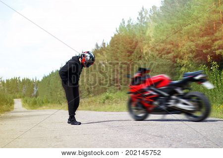 Motorcyclist In Helmet Looks At The Red Sports Motorcycle. The Bike Is Blurred. Solar Photography