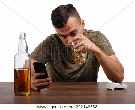 A drunk guy dependent on alcohol with a telephone, pack of cigarette and a glass of booze, isolated on a white background. A man suffers from alcoholism. A concept of fear, depression, and loneliness.