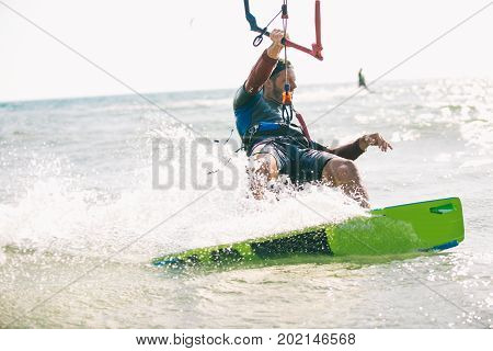 Kitesurfing Kiteboarding action photos man among waves quickly goes