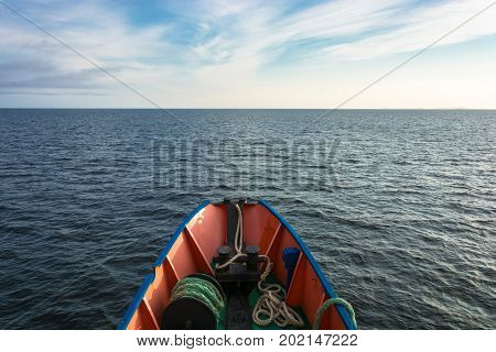 The nose of a small ship and the boundless calm of the White sea in an evening summer day.
