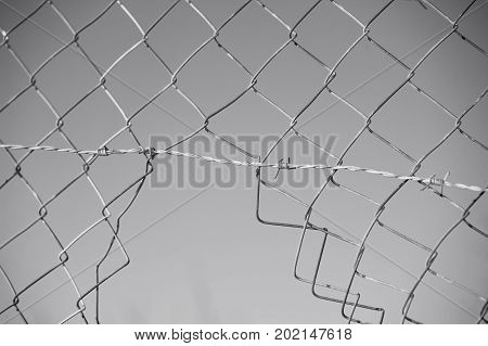 Cut fence with barbed wire in black & white
