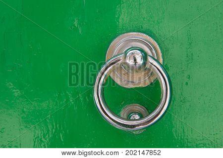Silver Door Knocker On A Green Wooden Door