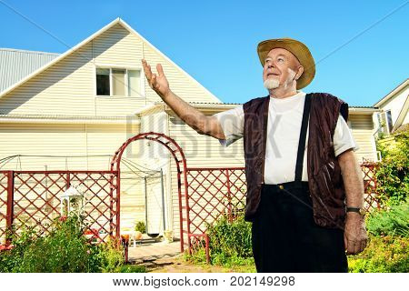 Happy retired senior man,  full of health, standing in his garden near the house. Sunny summer day.