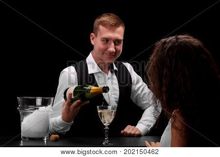An elegant bartender and a charming woman with curly hair flirting and smiling each other on a saturated black background. A bar worker pouring sparkling champagne on a glass. Nightclub or restaurant.