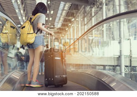 Young girl asian traveler holding phone with carrying hold suitcase luggage and passenger for tour travel booking ticket flight in airport international vacation time in holiday rest and relaxation.