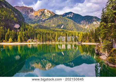 Magnificent lake Lago di Braies, South Tyrol. The emerald smooth surface of water reflects wood and mountains in coast of the lake. The concept of walking and eco-tourism