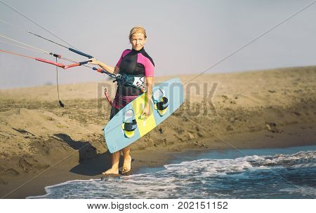 Beautiful Caucasian woman sufrer holding control bar and kiteboard and standing by the sea.