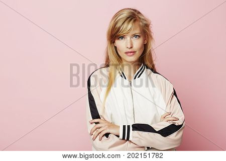 Beautiful blond lady in pink varsity jacket portrait