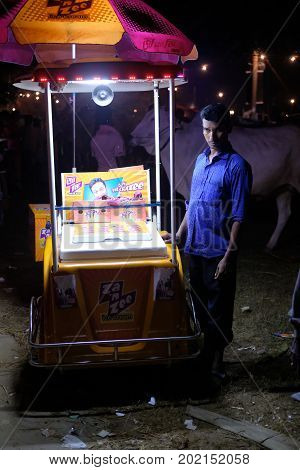 Dhaka, bangladesh, august 2017. a young man selling ice creamat local play ground for upcomming eid ul adha muslim festival located at aftab nagar cow market in dhaka in bangladesh taken on 30, august 2017.