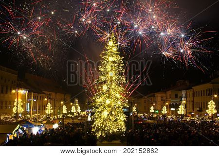 BANSKA BYSTRICA, SLOVAKIA - JANUARY 1, 2017: New Year`s Eve firework behind Christmas tree. Celebrating 2017 in Banska Bystrica, Slovakia. Multicolor explosion on dark sky. Foundation day of Slovak republic