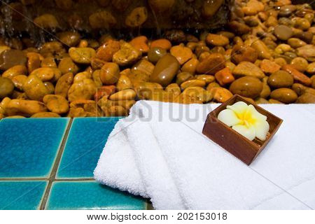 Spa set with towel and flower candle on the green tile floor with a lot of rocks