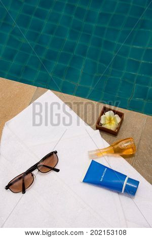 Sunglasses, bath towel, sunblock cream, bath gel and candle flower shape as spa set near the swimming pool