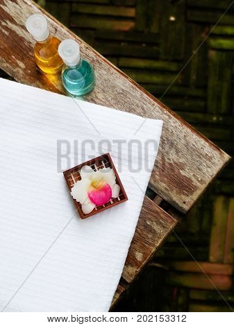 Bath towel, bath gel and candle flower shape as spa set on wooden floor in the garden
