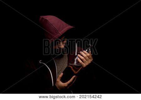 A drunk young guy dependent on alcohol with a bottle of scotch on a saturated black background. A male in the dark red hood suffers from alcoholism. The concept of fear, loneliness, and depression.