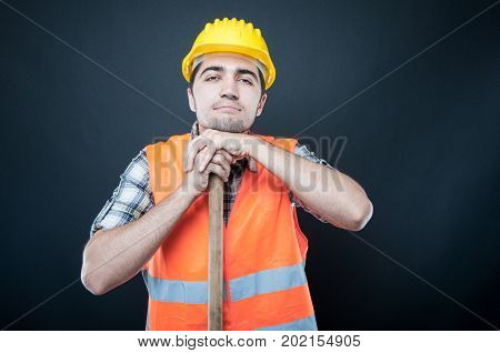Constructor Wearing Equipment Resting On Hoe Tool