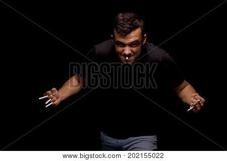 A portrait of a male with a lot of cigarettes in his hands on a saturated black background. A man depends on cigarettes. A guy struggles with addiction. Passive smoking concept.