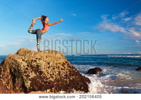 Meditation on sunset sky background. Young active woman stand in yoga pose on beach rock to keep fit and health. Healthy lifestyle outdoor fitness sport activity on summer family holiday.