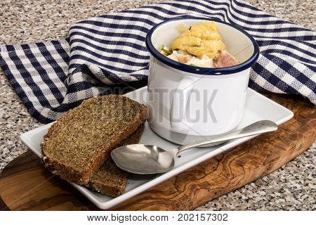 fish soup with smoked fish and bacon in an enamel cup