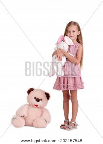 A delightful little girl is embracing big soft rabbit toy, isolated on a white background. A happiness kid in a pink dress hugging a plaything. A big teddy bear near a child. Childhood, toys concept.