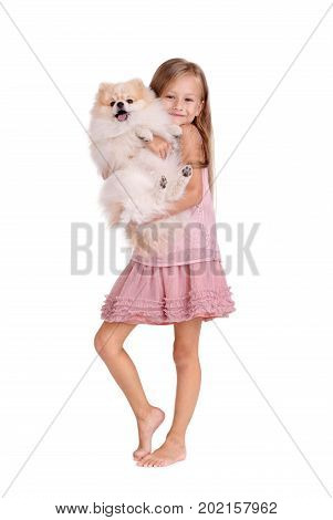 Full-length photo of a charming and happy little girl with a fluffy puppy, isolated on a white background. A cute baby girl with long hair in a pink dress is hugging a small dog. Copy space.