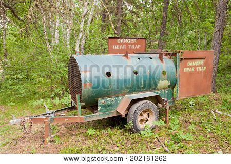 Live bear trap mobile trailer container deployed in forest wilderness to catch nuisance bear for relocation
