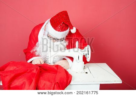 Santa Claus and sewing machine. Retro style. Christmas.