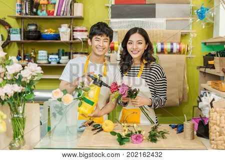 Male and female florists with beautiful bouquets in flower shop.