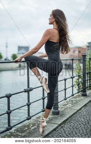 Beautiful ballet dancer stands on the river embankment and holds her hands and a left knee on the metal fence on the cityscape background. She wears a black top with leggings and light ballet shoes.
